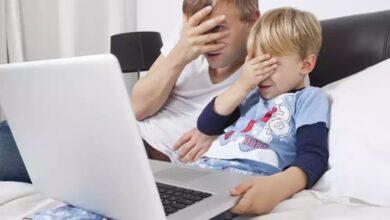 Un homme et un enfant cachent leurs yeux devant l'ordinateur