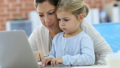 Une mère et sa fille utilisent un ordinateur à la maison